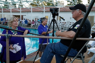 Jeanne Mayer confers with camera operator Jim Rphrs (right) as Village audio expert Paul Shiki gets sound system ready. Photo: Fred Harshbarger